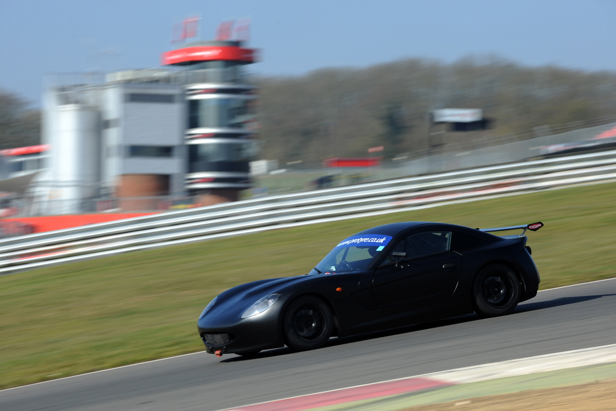 Matt Chapman driving his matte black Ginetta G40 GT5 car down paddock hill Brands Hatch