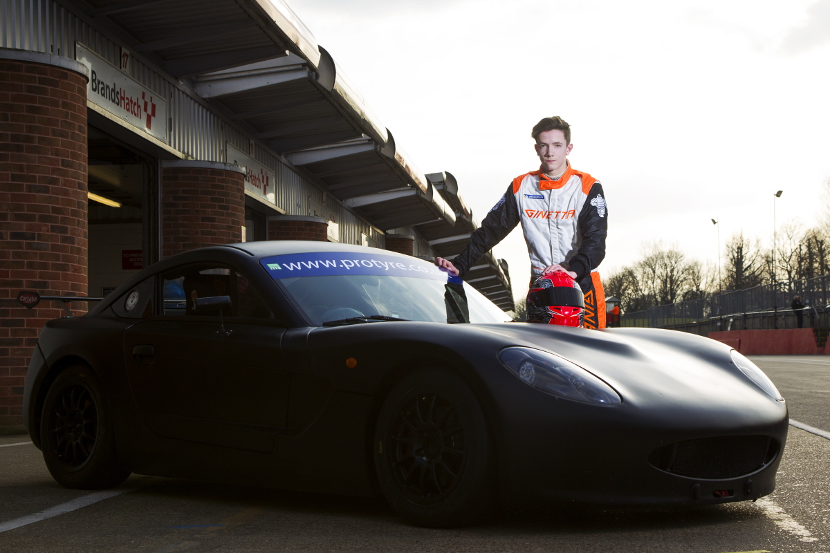 Matt Chapman standing next to his matte black Ginetta G40 in the pit lane of Brands Hatch